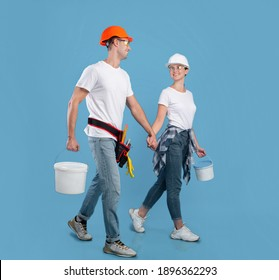 Young spouses in safety glasses and hardhats walking with paint equipment over blue background, millennial workers couple ready for apartment repair and house renovation, full length shot, copy space
