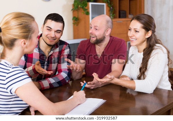 Young spouses sitting with documents and asking russian friends for advice