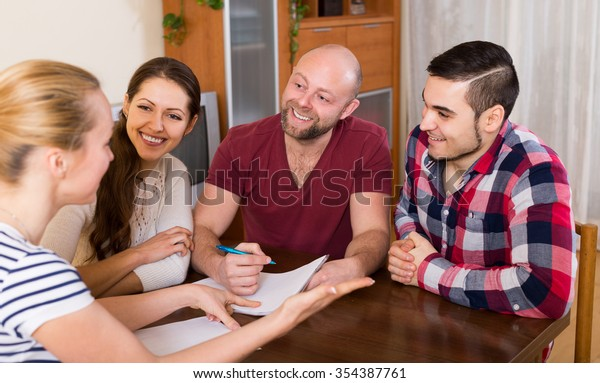 Young spouses sitting with documents and asking european friends for advice