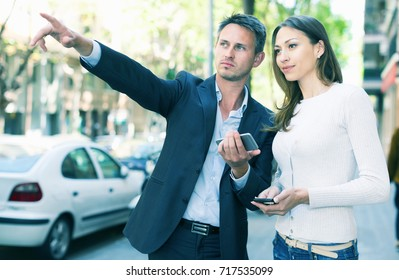 Young spouses strolling through city streets and pointing each other something