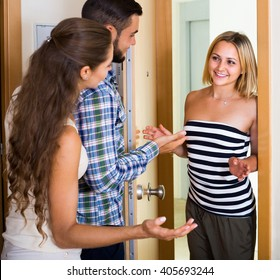 Young spouses welcoming smiling friend at the doorway