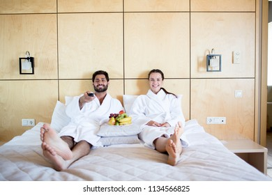 Young spouses in white soft bathrobes lying on bed in bedroom of their new house or hotel room