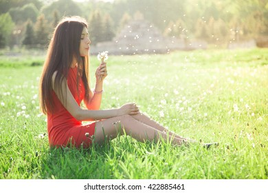 Young spring fashion woman blowing dandelion in spring garden. Springtime. Trendy girl at sunset in spring landscape background.