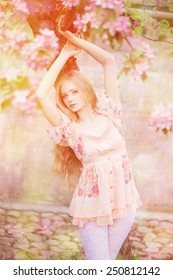 Young spring fashion woman  in spring garden. Springtime. Trendy girl at sunset in spring landscape background. Allergic to pollen of flowers. Spring allergy