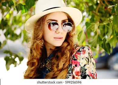 Young spring fashion woman posing in city street. Springtime. Trendy hipster girl wearing vintage sunglasses, hat and jacket, curly long hair.