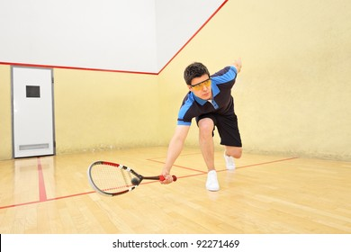 A young squash player hiting a ball in a squash court