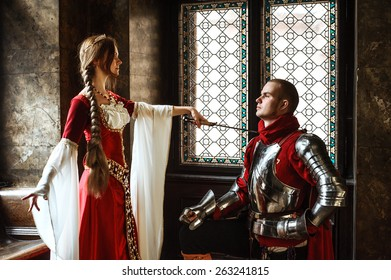 A young squire being awarded knighthood by a noble lady.