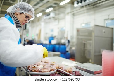 Young staff sorting seafood into plastic containers while standing by processing line in factory