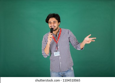 Young standing man holding the microphone raising his hand talking on a green background.