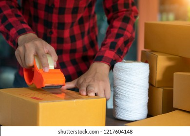 young start up small business owner packing cardboard box at workplace. freelance woman seller prepare parcel box of product for deliver to customer. Online selling, e-commerce, shipping concept