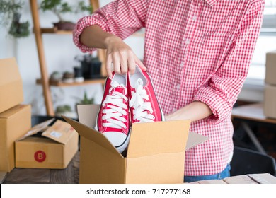 young start up small business owner packing shoes in the box at workplace. freelance woman seller prepare product for packaging process at home.  Online selling, internet marketing, e-commerce concept