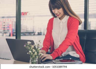 young start up woman wearing red cardigan typing on computer at home. freelance female adult working with laptop at cafe. education, business concept.