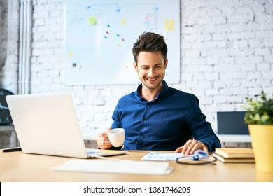 Young startup businessman drinking coffee and working using laptop and documents