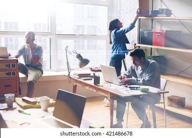 Young startup group working in modern office. Open space, laptops and paperwork. Film effect, blurry background, lens flare effect