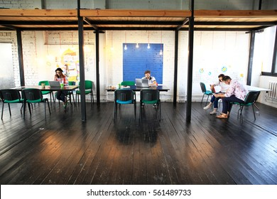 Young startup group working in modern office. Open space, laptops and paperwork.