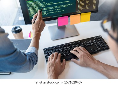 Young startup Programmers Sitting At Desks Working On Computers screen for Developing programming and coding to find solution to problem on New Application