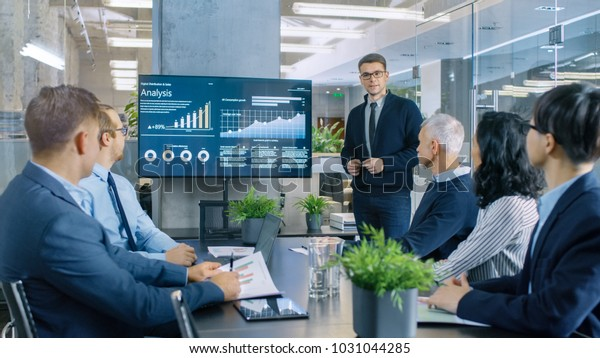 Young Stock Trader Shows to the Executive Managers Cryptocurrency and Trade Market Correlation Pointing at the Wall TV.