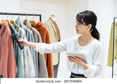 Young store clerk reading data of clothes. Inventory management. Stocktaking. RFID.