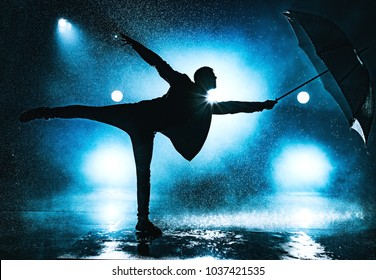 Young strange man dancing with umbrella under the rain. Dramatic blue colors.