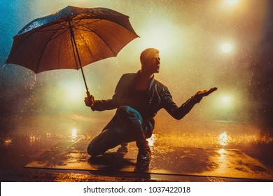 Young strange man with umbrella under the rain. Vibrant lights on background.