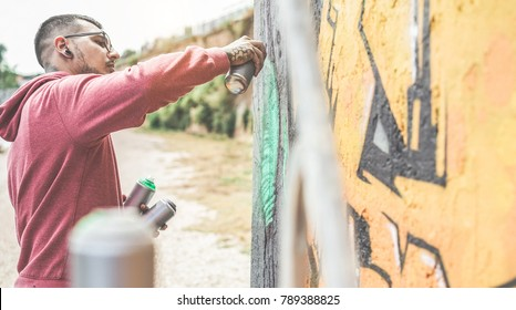 Young street artist painting with color spray on the wall - Contemporary graffiti artist at work - Urban lifestyle, modern street art and youth concept - Focus on face hand