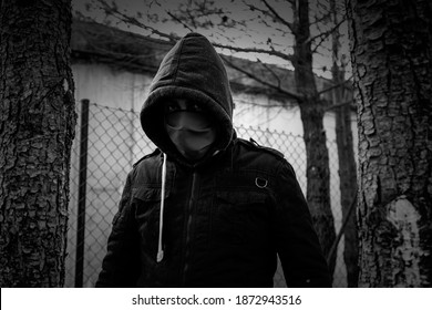 Young street gang with mask in park, social problem