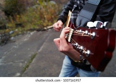 Young street musician playing acoustic guitar