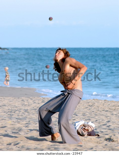 Young street performer juggeling on a California Beach