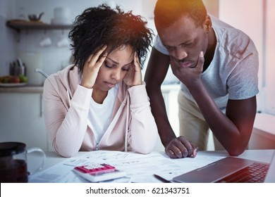 Young stressed african american couple in trouble, have no money to pay debts,  rent for appartment. Wife holding head in despair, having financial troubles. Household budget