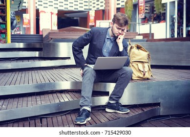 young stressed businessman sitting with laptop computer for working at outdoor. Stressed businessman concept.