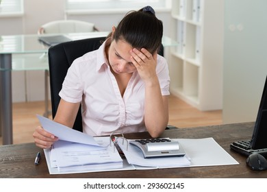 Young Stressed Businesswoman Checking Bills In Office