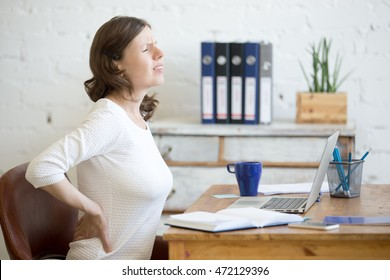 Young stressed businesswoman sitting in front of laptop and holding her waist with pained expression. Business woman feeling pain, touching aching back, suffering from backache after working on pc