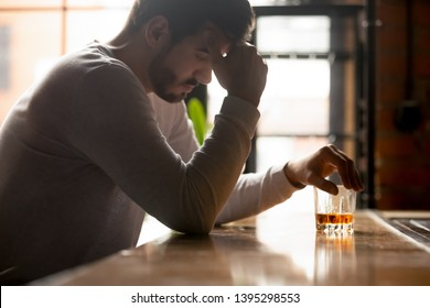 Young stressed drunk man sitting alone with glass of whiskey in bar in the morning, thinking about problem at work or relationships, feeling lonely and unhappy, alcohol addiction concept