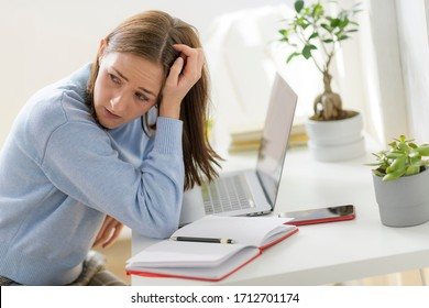 young stressed female sitting in home office