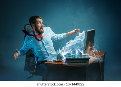 Young stressed handsome businessman working at desk in modern office shouting at laptop screen and being angry about e-mail spam. Collage with a mountain of crumpled paper. Business, internet concept