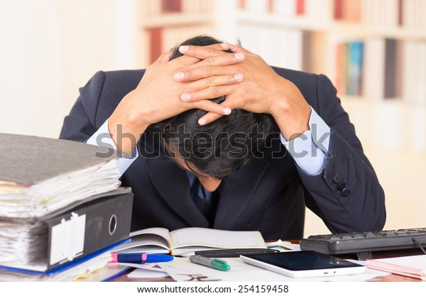 young stressed overwhelmed business man with piles of folders on his desk holding his head looking down