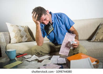 young stressed and overwhelmed man biting calculator holding mess of bank and receipts paperwork desperate calculating monthly expenses taxes and income frustrated in domestic accounting