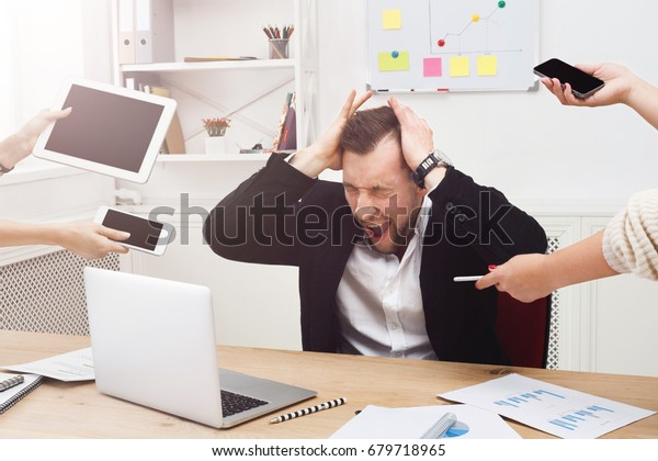 Young stressed and overworked business owner. Businessman in modern office scream, upset with employees ask for attention with devices. Unhappy worcaholic job problems concept.