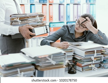 Young stressed secretary in the office overwhelmed by work and desk full of files, her boss is bringing more paperwork to her