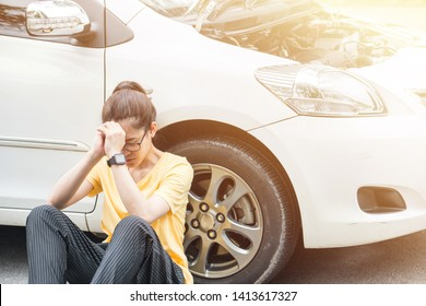 Young stressed woman having trouble with her car breakdown on the road and she waiting someone can help her. Conceptual of car accident on the road.