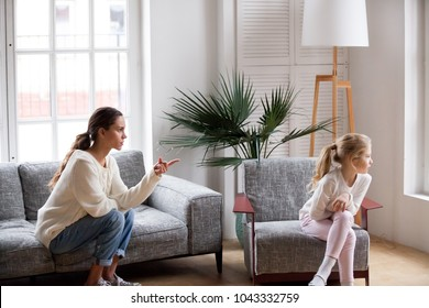 Young strict mother or sister scolding stubborn sulky kid girl in living room at home, offended daughter ignoring angry mom reprimanding disobedient child for bad behavior, family conflict concept