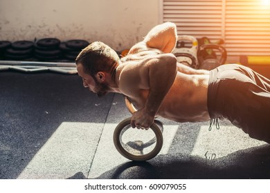 Young stron man is doing push-ups by rings.