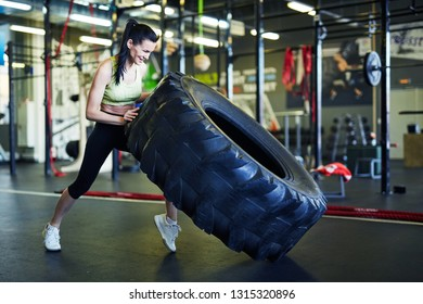 Young strong active woman in sportswear lifting big heavy tyre while training in leisure center