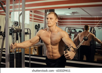 Young strong athlete with a beautiful naked torso doing muscle exercises in the gym
