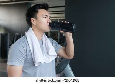 Young and strong athlete drinking protein shake