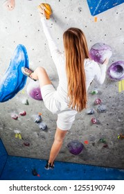 Young strong beautiful blonde long hair girl climbing indoor