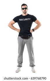 Young strong bouncer in sporty clothes with arms on hips looking at camera. Full body length portrait isolated on white studio background.