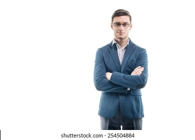 Young strong businessman  in fashionable suit stands against the wall with hands crossed