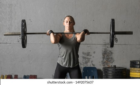 Young strong female powerlifter training in gym, closeup shot.