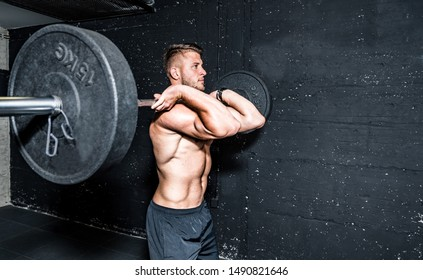 Young strong fit muscular sweaty man with big muscles doing barbell weight lifting cross training workout in the gym dark image real people